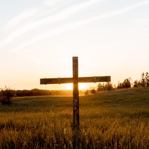 A weathered cross sits in a grassy field
