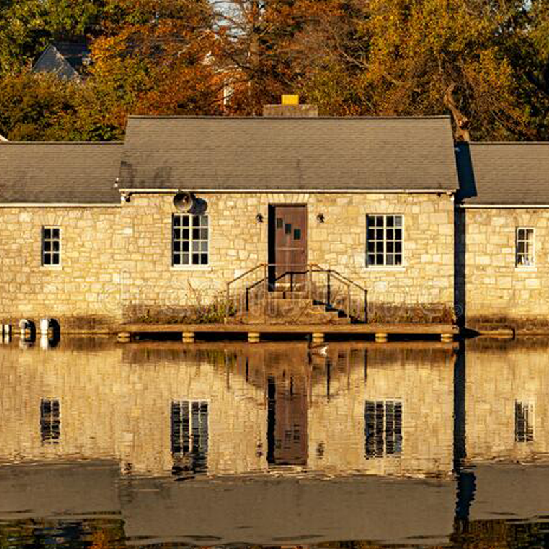 A Stone building reflected on the face of a body of water